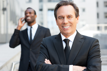 Expert in business world. Confident senior man in formalwear keeping arms crossed and smiling while African man talking on the mobile phone in the background   photo