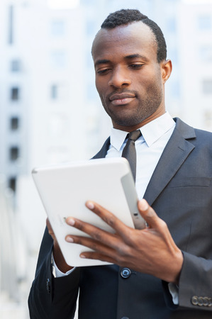 Businessman with digital tablet. Confident young African man in formalwear working on digital tablet and while standing outdoors photo