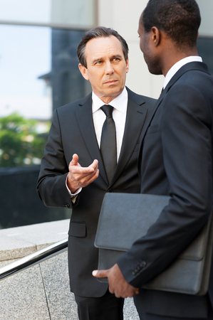 Talking about business. Two confident business men talking and gesturing while standing outdoors  photo