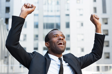 Business winner. Happy young African man in formalwear keeping arms raised and expressing positivity while standing outdoors photo
