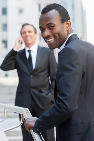 Confident businessman. Cheerful young African man in formalwear moving up by stairs and looking over shoulder while senior man talking on the mobile phone in background   photo