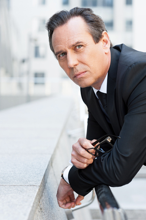 near side: Lost in business thoughts. Side view of thoughtful mature man in formalwear holding glasses near face and looking away while standing outdoors Stock Photo