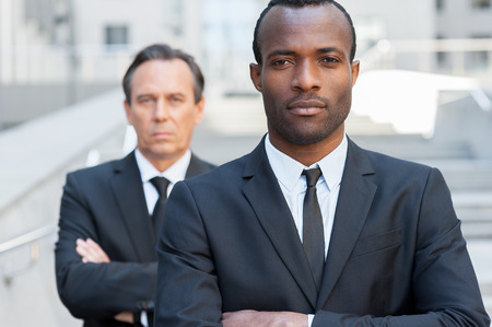 自信を持ってビジネスの専門家。正装腕交差し、成熟したビジネスマンが彼の後ろに立っている間カメラ目線を維持に自信を持ってアフリカ人