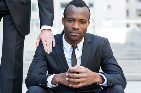 shoulder problem: He needs a friendly support. Frustrated young African man in formalwear sitting on staircase while someone touching his shoulder with hand