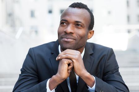 hombre pensando: Generar nuevas ideas geniales. Hombre africano joven alegre en ropa formal manteniendo las manos juntas y mirando a otro lado mientras se est� sentado en la escalera al aire libre Foto de archivo