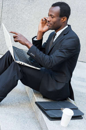 Busy working outdoors. Side view of confident young African man in formalwear talking on the mobile phone and working on laptop while sitting outdoors photo