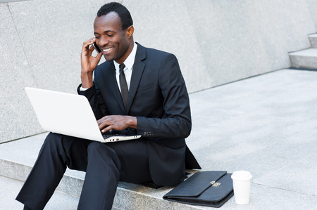 Business is his life. Cheerful young African man in formalwear talking on the mobile phone and working on laptop while sitting on outdoors staircase photo