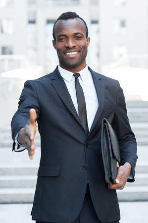 Welcome on board! Handsome young African man in full suit stretching out hand for shaking while standing outdoors