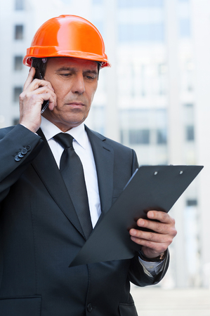Busy contractor. Confident mature man in formalwear and hardhat talking on the mobile phone and looking at clipboard while standing outdoors photo
