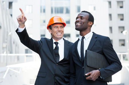 businessman standing: Showing opportunities. Cheerful contractor in hardhat pointing away and smiling while standing together with African businessman