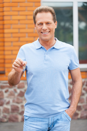 Handsome mature man standing in front of a house holding a key photo
