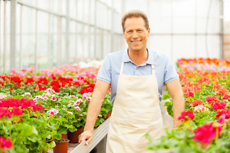 Handsome mature man standing in flower bed and smiling