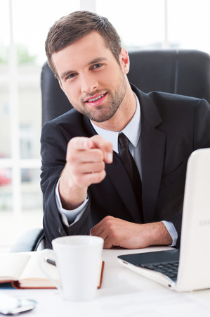 easier: Making business easier. Confident young man in formalwear pointing you and smiling while sitting at his working place