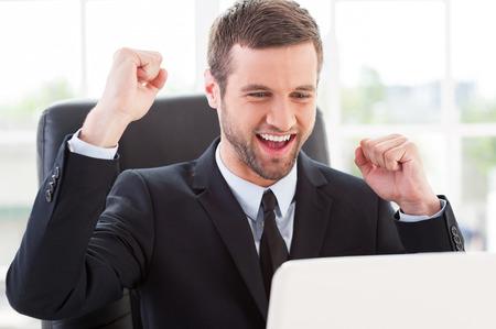 Yo lo hice! Hombre joven feliz en ropa formal mirando el monitor del ordenador y gesticulando mientras estaba sentado en su lugar de trabajo Foto de archivo