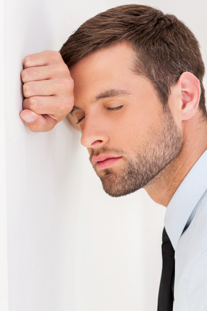 Sick and tired. Side view of depressed young man in shirt and tie leaning at the wall and keeping eyes closed photo