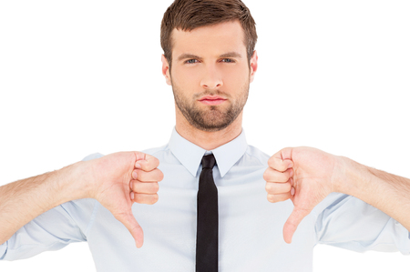 stubble: Rejected! Portrait of confident young man in shirt and tie looking at camera and showing his thumbs down while standing isolated on white background