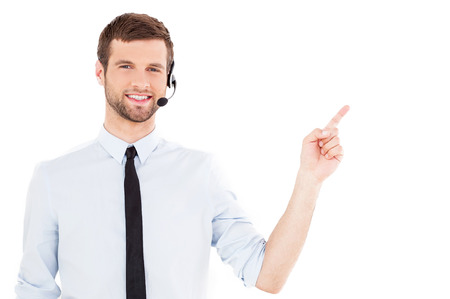 call center representative: Operator pointing copy space. Handsome young man in formalwear and headset looking at camera and pointing away while standing isolated on white background
