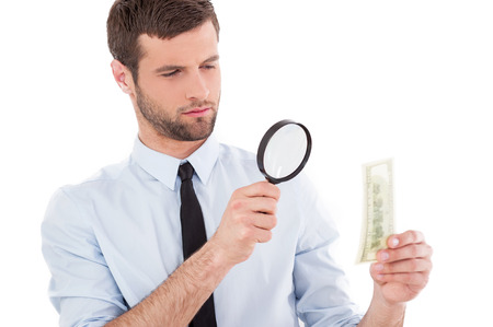 Fake or real? Serious young man in shirt and tie looking through a magnifying glass at the paper currency while standing isolated on white background  photo