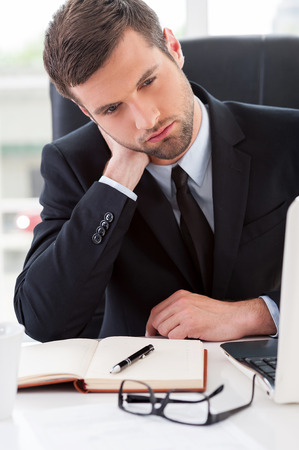 Tired businessman. Frustrated young man in formalwear looking away and touching his neck with hand while sitting at his working place