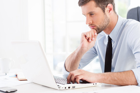 working place: Concentrated on work. Side view of thoughtful young man in formalwear looking at laptop and holding hand on chin while sitting at his working place Stock Photo