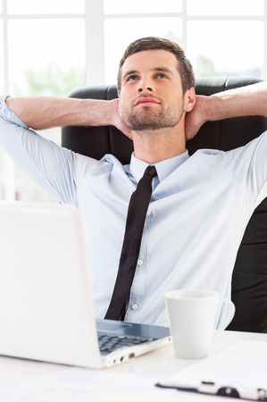 head collar: Day dreaming in office. Handsome young man in shirt and tie holding hands behind head and smiling while sitting at his working place Stock Photo