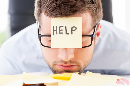 frustrace: Potřebuje pomoc. Frustrovaný mladý muž v formalwear s lepící Poznámka na čelo opíral hlavu na stůl Reklamní fotografie