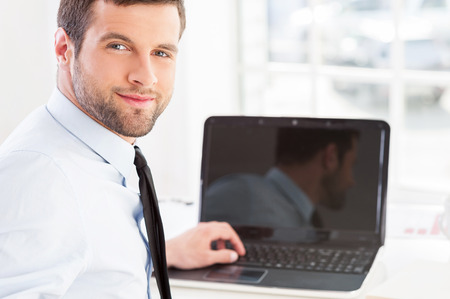 How may I help you? Handsome young man in formalwear working on laptop and looking over shoulder while sitting at his working place photo