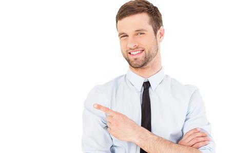 実業家ポインティング コピー スペース。シャツとネクタイ カメラ目線と、白い背景で隔離に立っている間指すでハンサムな若い男