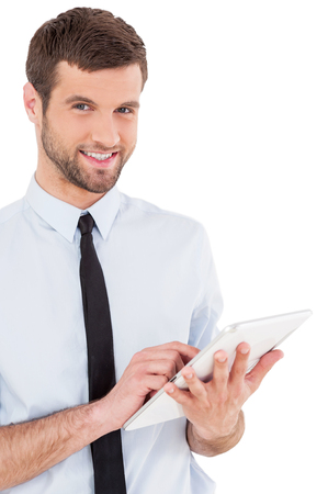 Examining his new gadget. Cheerful young man in formalwear working on digital tablet and smiling while standing isolated on white background photo