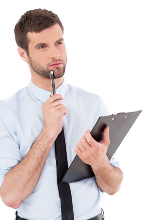 Businessman with clipboard. Thoughtful young man in formalwear holding clipboard and touching his chin with pen while standing isolated on white background