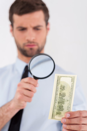 Fake or real? Concentrated young man in shirt and tie looking through a magnifying glass at the paper currency while standing isolated on white background  photo