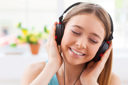 Day dreaming with her favorite music. Cheerful teenage girl in headphones listening to the music and keeping eyes closed while sitting in her apartment photo