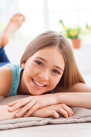 Relaxing at home. Cheerful teenage girl smiling at camera while lying on the floor at her apartment