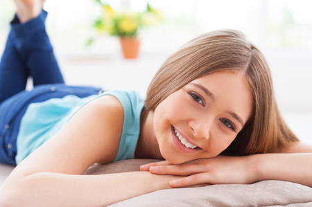 Relaxing at home. Cheerful teenage girl smiling at camera while lying on the floor at her apartment photo