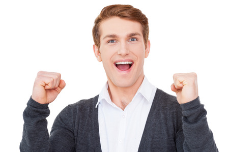 good news: I won! Happy young man keeping arms raised and looking at camera while standing isolated on white