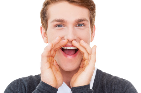 mouth closed: Sharing good news. Happy young man keeping arms raised and looking at camera while standing isolated on white  Stock Photo