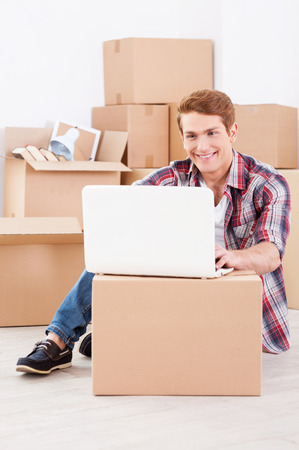 Searching a moving company in the net. Cheerful young man sitting on the floor and working on laptop while cardboard boxes laying in the background photo