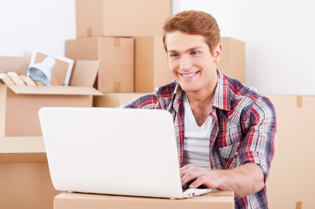In search of a good moving company. Handsome young man sitting on the floor and working on laptop while cardboard boxes laying in the background photo