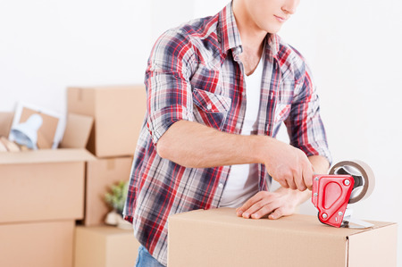 Preparing to moving. Close-up of man packing boxes while other cardboard boxes laying in the background photo