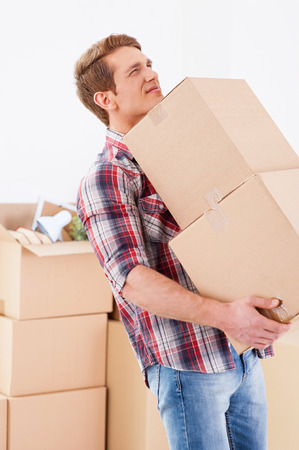 Too heavy boxes. Young man carrying the heavy boxes and expressing negativity while other cardboard boxes laying in the background photo