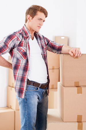 expressing negativity: Feeling pain in back. Young man holding hand on his back and expressing negativity while leaning at the cardboard box