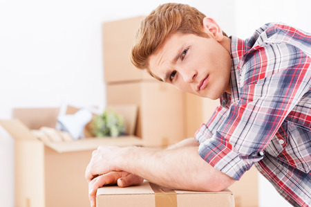 expressing negativity: Tired of moving. Side view of depressed young man leaning at the cardboard box and expressing negativity while more boxes laying in the background