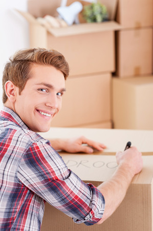 Marking a carton box. Top view of cheerful young man marking a cardboard box and looking over shoulder while more boxes laying in the background photo