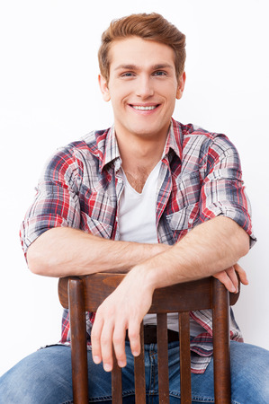Casually handsome. Handsome young man smiling while sitting on the chair and against white background photo