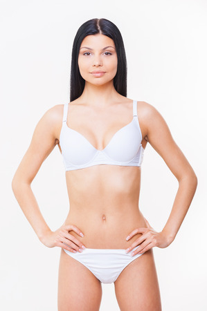 hands on hips: Young and healthy. Attractive young woman in white bra and panties holding hands on hip and looking at camera while standing isolated on white