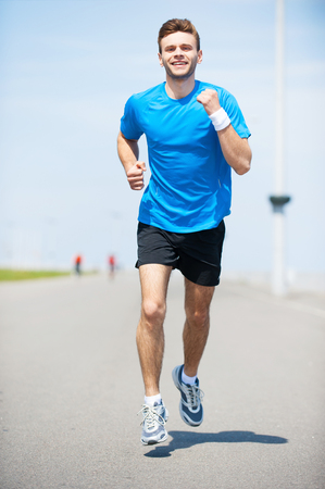 man front view: I love running. Full length front view of handsome young man running along the road and smiling