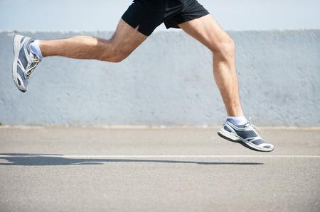 pista de atletismo: La quema de los kil�metros de distancia. Vista lateral cerca de la imagen del hombre correr al aire libre Foto de archivo