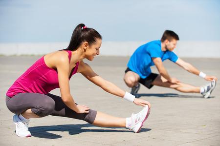 actividad fisica: El ejercicio juntos es divertido. Joven y bella mujer y el hombre haciendo estiramientos ejercicios juntos mientras que de pie al aire libre Foto de archivo