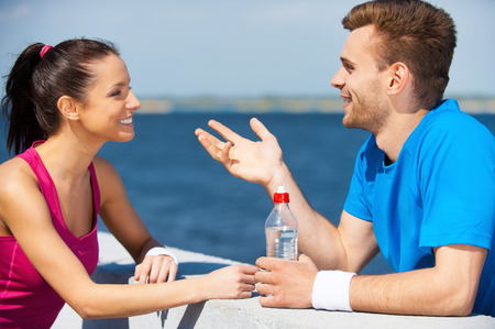two people talking: Sport connecting people. Side view of beautiful young couple in sports clothing standing face to face and talking