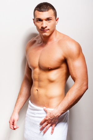 Women love me. Confident young shirtless man covered with towel looking at camera while standing against grey background photo